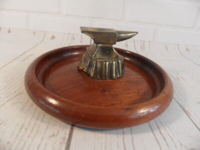 small vintage nut cracker -- anvil -- on a wooden bowl