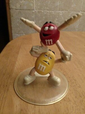 M&M Candy Yellow Holding up Red Candy Display