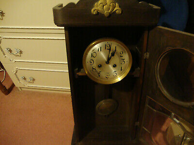 Large antique wall clock with pendulum movement in a lovely dark wooden case