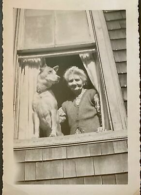 """Snapshot woman and her dog looking out of window (3 1/2"""" by 5"""")"""