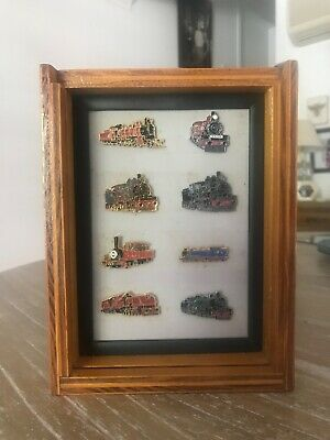 Queensland Rail locomotive badges (x8) in plywood display case. Felt stained.