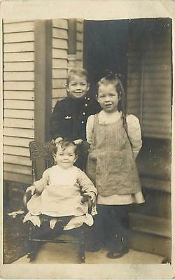 REAL PHOTO-THREE CHILDREN POSING OUTSIDE-BABY IN ROCKING CHAIR-SIBLINGS-K70297