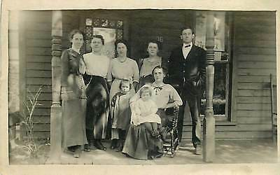 REAL PHOTO-GROUP ON PORCH-WOMAN HOLDING BABY IN ROCKING CHAIR-K81341