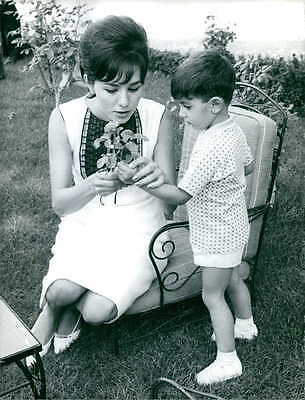 Vintage photo of Farah Pahlavi taking flower from her son's hand.  -