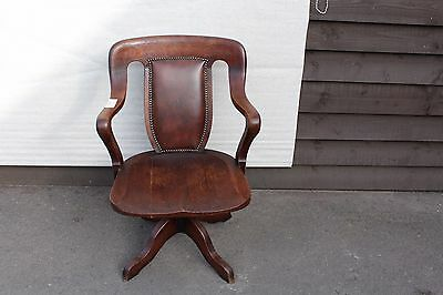 1920's Leather Oak Office chair. Leather back . On castors.