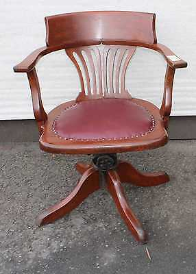 1920's Leather Oak Office chair. Leather Seat carved back . On castors.