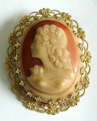 A Vintage Resin Cameo Brooch With A Gold Tone Filigree Mount