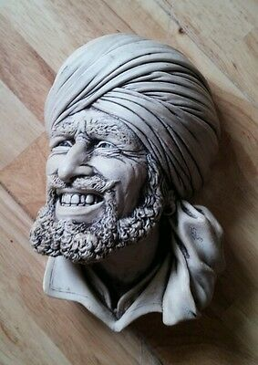 Wall hanging face mask of man with head covering possibly an arabic man