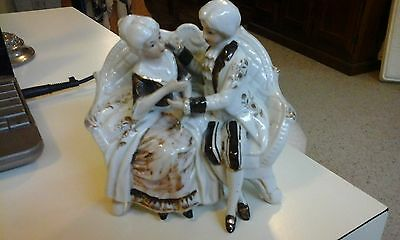 white porcelain man&woman figurine sit inchair white and brown clothes gold trim