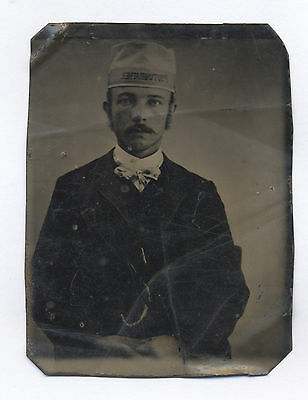 Ca. 1860's-1880's TINTYPE: MAN WITH THE WORD PHOTOGRAPHER ON HIS HAT