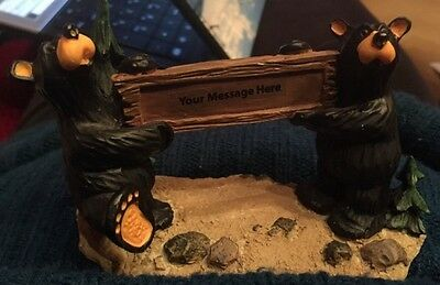 Big Sky Carvers Jeff Fleming Bearfoots 2 Bears holding sign for message