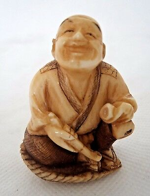 JAPANESE MEIJI c1900 NETSUKE - MAN SMILING WITH PIPE ON MAT - SIGNED