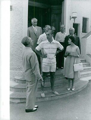 Vintage photo of Farah Pahlavi standing with men on doorstep and talking.