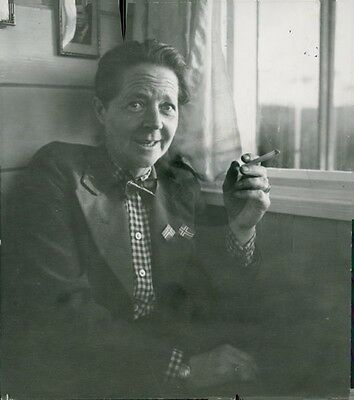 Vintage photo of A man siting beside of the window while smoking a tabacco durin