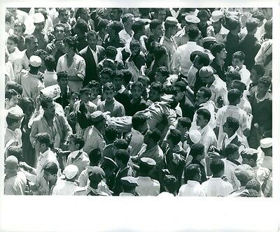 Vintage photo of A fainted man being carried among huge crowd during the funeral