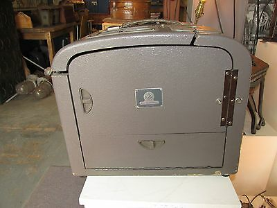 A vintage Bell and Howell 621 projector case with speaker and dust cover