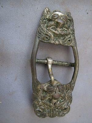 Old decorative white metal buckle in the form of 2 Lion head masks.