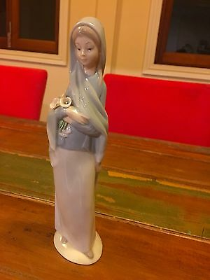 Lladro figurine of woman holding lillies. Imperfect.