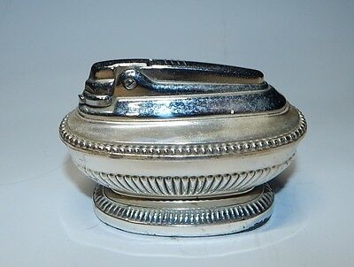 Silver butane cigar and cigarette lighter, sits on table, made in England