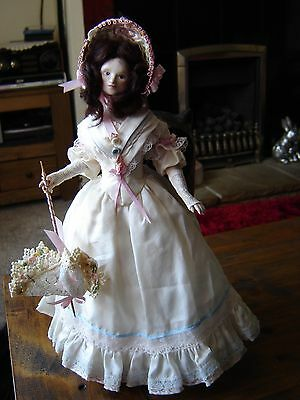 "Beautiful Porcelain doll in period clothing. Silk dress. Approx 12"" tall."