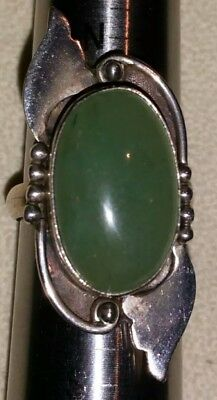 Vintage 1970s Unusual silver tone ring set with a green glass cabochon stone.