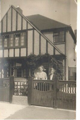 1934  view of 2 people  in front of a house. Card posted in Ealing.