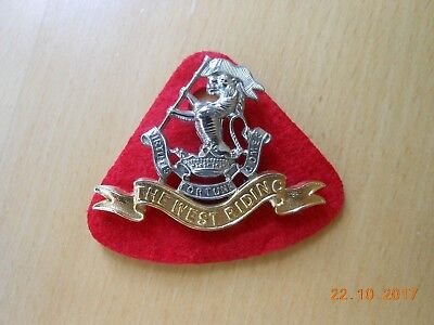 The West Riding Regiment cap badge with slider -red cloth backing