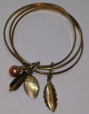 Vintage 1970s gold tone joined bangles x 3 with charms.  Costume jewellery.