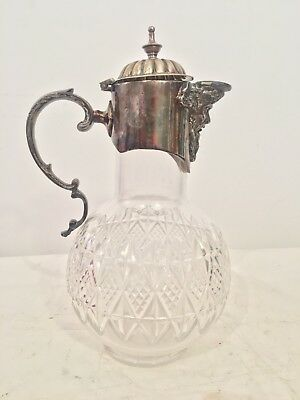 A cut glass claret jug with silver plated mounts and mask spout Finely Detailed