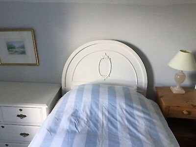 Pair of antique single bedsteads with white painted rounded head and footboards.
