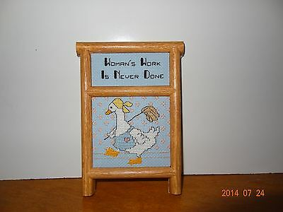 """Finished Cross stitch framed plaque that says """"Woman's work is never done"""""""