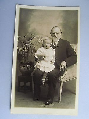 vintage Postcard, baby girl on older man's knee, suit, tie, chair, B&W photo,
