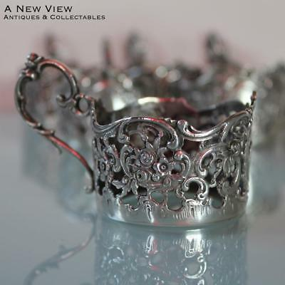 Six Rococo style German silver floral cup holders.
