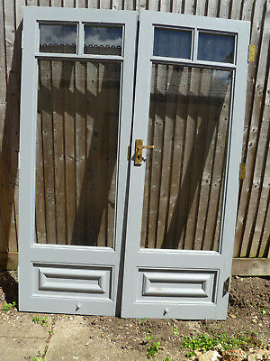 Pair of wooden glazed French doors with brass fittings including locks