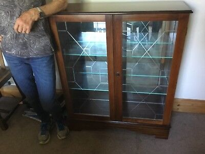 Glass fronted wooden display cabinet with mirror back.