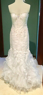 New white wedding gown. Size10. Ruffled skirt.Strapless. Lace up back.Train