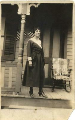 Rppc Vintage photo of Woman on porch with 2 American flags behind
