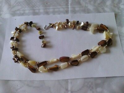 A very old necklace, white and brown beads with pearls in between. 27 inches  .
