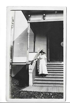 Vintage RPPC Postcard-Woman in a white dress standing on a staircase