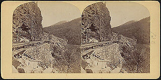 Photo:Railroad tracks on a mountainside, supported by a stone wall