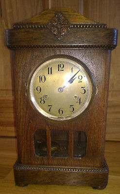 Mantle Clock with 8-day duration, oak case, silvered dial.