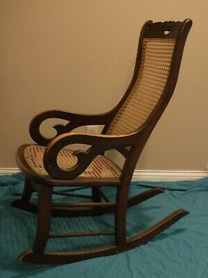 Antique 19th C Solid Wood Lincoln Rocking Chair w Caned Seat & Back Carved Top