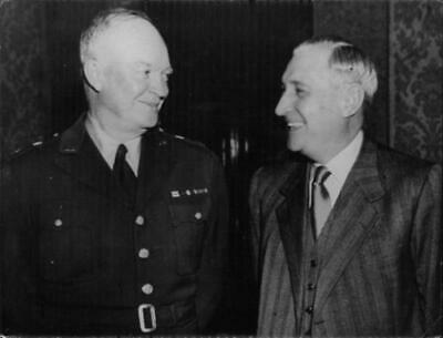 """American politician Dwight David """"Ike"""" Eisenhower in uniform standing with a man"""