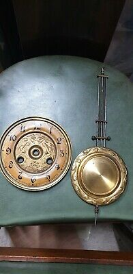 Antique clock face together with matching pendulum