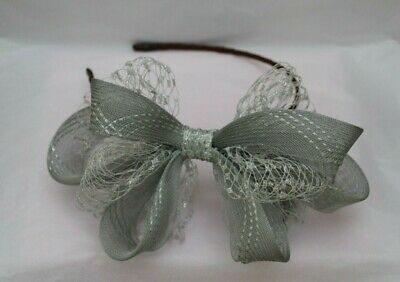Silver metallic net and grey fascinator on a brown ribbon headband
