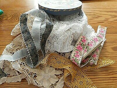 Hand painted vintage box filled with antique laces and embroideries.