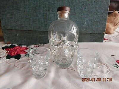Crystal Head Vodka clear glass skull decanter and 2 shot glasses.  No alcohol.