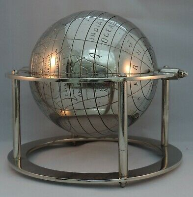 A steel desktop globe having engraved details set within a gimbal raised on a...