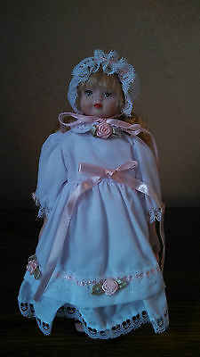 Bisque Porcelain Doll, White Dress/Bonnet trimmed in lace w/pink ribbon & roses