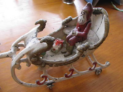 Cast iron toy Santa in sleigh pulled by two reindeers. Wheels on both pieces